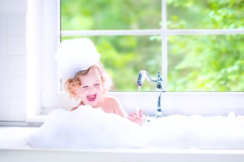 Child having a bath in the kitchen sink with lots of bubble