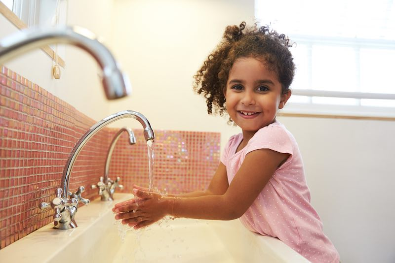 Child washing hands in a sink