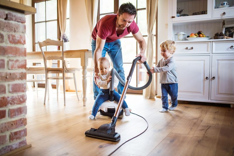Dad with 2 children vacuuming their dining room floor