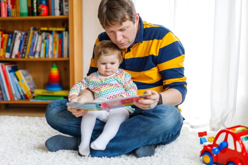 Baby reading with dad